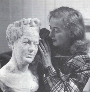 Betty working on a bust of Gracie (inn her best clothes).